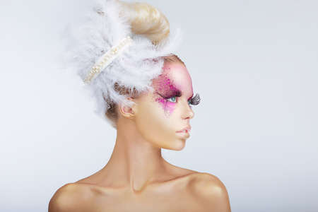 swanky: Creativity. Glamorous Fashion Model with Fancy Hair-do with Feathers Stock Photo