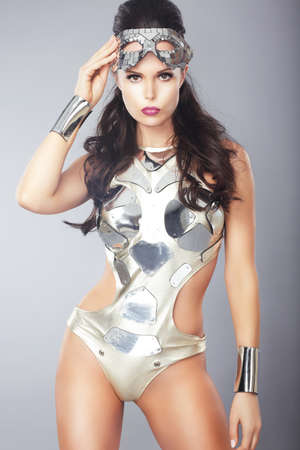party outfit: Splendor  Ultramodern Woman with Metallic Mask in Trendy Costume Stock Photo