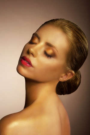 Artistry. Fanciful Bronzed Womans Face. Futuristic Art Gold Makeup