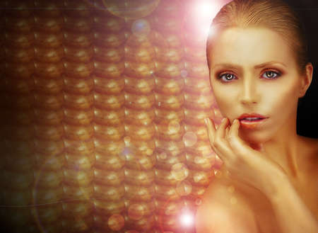 Fantasy  Beautiful Woman over Sparkling Gold Background photo