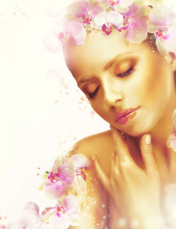 maquillaje fantasia: Cutis. Mujer magn�fica con el perfecto bronceado de la piel y de la orqu�dea Flores. Fragancia Foto de archivo