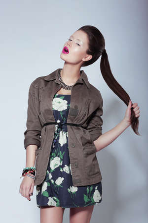 tress: Trendy Fashion Model in Elegant Clothes holding her Tress