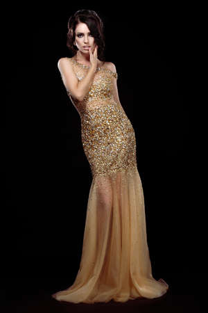 evening gown: Elegance. Aristocratic Lady in Golden Long Dress over Black Background