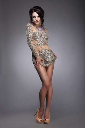 flirtatious: Glamorous Graceful Lady in Silver Festive Dress Smiling Stock Photo