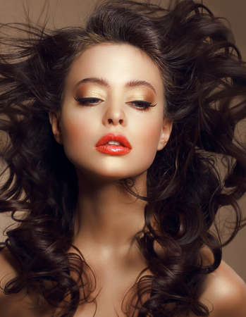 Sexy Woman with Long Windy Brown Hair and Saturated Makeup photo