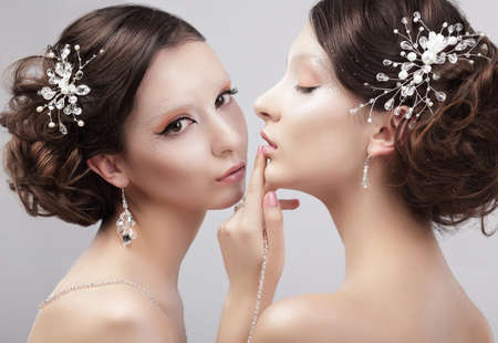 Sensuality. Two Women Fashion Models with Trendy Make-up photo