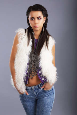 snazzy: Stylish Young Woman in Modern Furry Jacket and Jeans Stock Photo