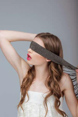 woman tied: Hide and Seek. Woman Holding a Strap on her Face. Puzzle
