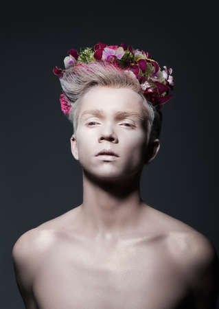 exotism: Beauty. Young Man with Wreath of Flowers over Gray