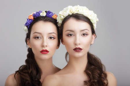 우아함. 꽃의 화환을 가진 두 여자. 공상