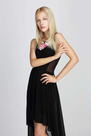 Sophisticated Lady in Black Silky Evening Dress Gracefully Posing photo