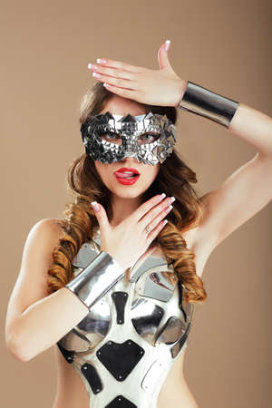 stagy: Futurism. Robotic Woman in Cosmic Mask and Metallic Stagy Costume Gesturing Stock Photo