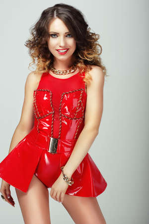 Glamor. Smiling Sensual Woman in Red Shiny Clothes photo