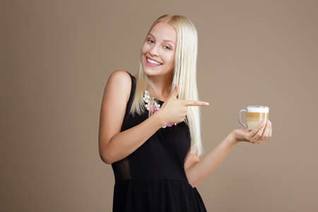 Happy Blond Woman Points Out to the Cup of Coffee photo
