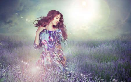 people and nature: Fantasy. Woman in Enigmatic Meadow over Cloudy Sky