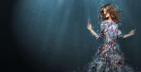 Onderdompeling. Vrouw in Deep Blue Sea. Fantasie Stockfoto