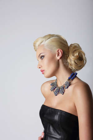 bouffant: Profile of Young Contemplating Blonde with Necklace Stock Photo