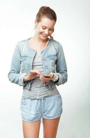 Young Woman in Jeans with Smartphone photo