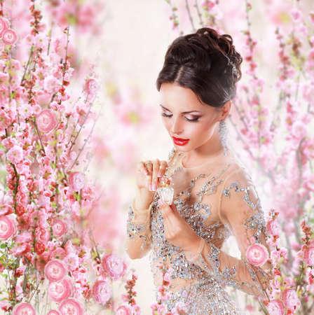 花の背景の上の香水と女性