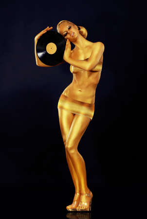 gold record: Woman Painted Gold With Vinyl Record Stock Photo