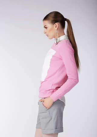 svelte: Stylish Girl in Shorts Posing in Studio Stock Photo