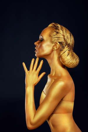 body paint: Mujer con cuerpo de oro sobre fondo Negro