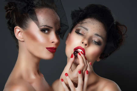 Lure. Two seductive Women with Cherry Berries photo