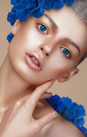 Portrait of Young Woman with Bronzed Skin and Blue Eyes Stock Photo