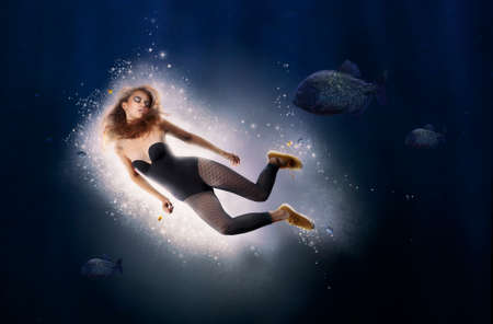 Creativity. Fantasy. Woman is Diving in Water photo