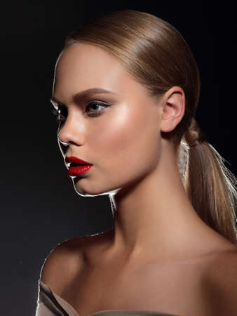 Sensual portrait of a beautiful glamor model woman with red lips with a clean healthy skin. Dark background. Stock Photo