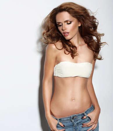 donna sexy: Bella sexy giovane donna in posa in studio. In costume da bagno e jeans.