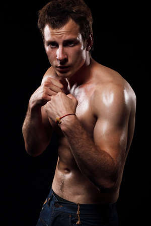 fighting stance: Portrait of muscular man with fighting stance against black background. Stock Photo