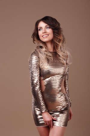Stunning smiling woman in luxurious glitter dress.
