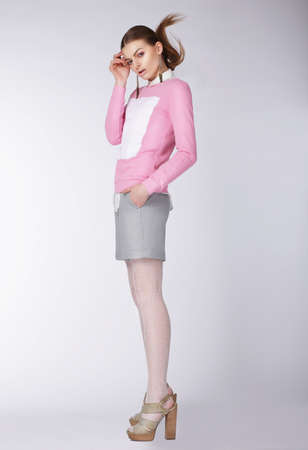 Young woman wearing casual clothes posing at studio. Full length. photo
