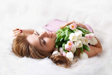 tulipan: Młoda kobieta z bukietem kwiatów na łóżku.
