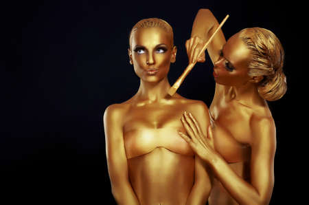 Two women painted in gold paint. photo