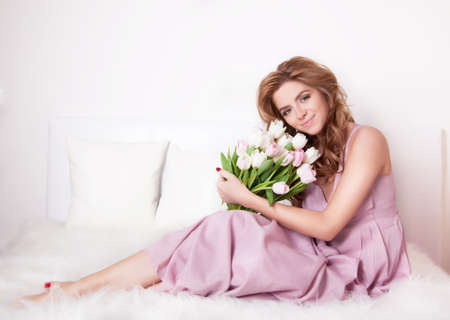 beautiful pink white flower: Beautiful smiling young woman sitting on a bed with a bouquet of flowers. Stock Photo