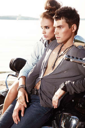 male and female: Romantic young couple in casual clothes sitting on a motorcycle. Stock Photo