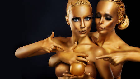 Portrait of a girl with golden body art posing with golden apple in her hands. photo