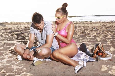 delito: Una mujer consuela a un hombre en la playa.