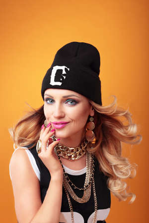 Hip-hop woman in cap with long  hair. Fashion portrait of modern girl in cap.