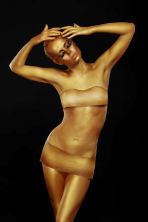 woman naked body: Golden woman posing in the studio. Stock Photo