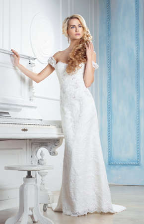 The bride in a long dress. Blonde, long braid hairstyle.