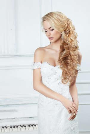 Portret van de bruid met lange lokken. In een witte jurk. Stockfoto