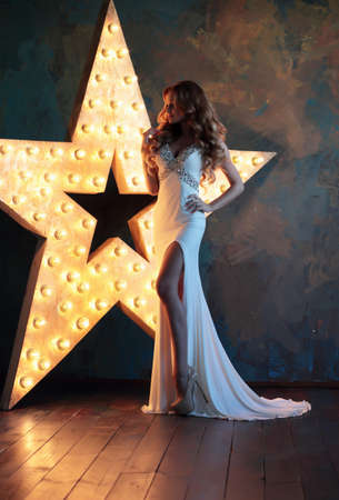 fashion model: A woman in a long dress evening is in full growth on a background of stars. Stock Photo