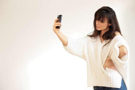 millennial: Girl taking selfie. Natural light.
