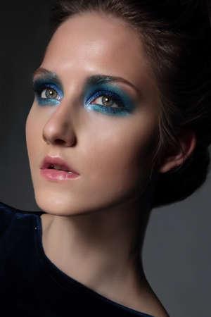 maquillaje de ojos: Mujer hermosa joven con retro maquillaje de fantasía. Brillante sombra de ojos azul. Cerca de cara hacia arriba.