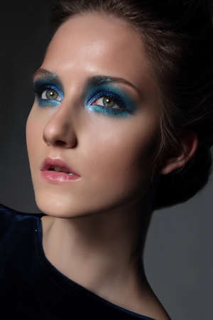 shadow face: Young beautiful woman with fancy retro make-up. Bright blue eye shadow. Face close-up.