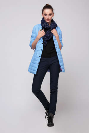 Young woman in a blue jacket with a scarf around his neck and pants, posing in studio full-length. Fashion.