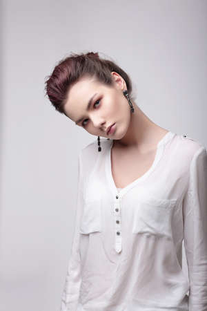 Fashionable woman in a white blouse looks into the camera.